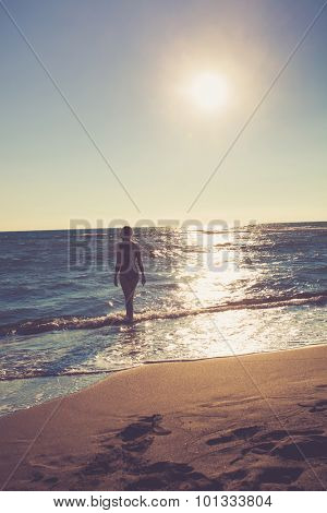 woman at bikini stand at sandy beach looking at horizon, sunny summer day, back view, retro colors, Ada Bojana, Montenegro