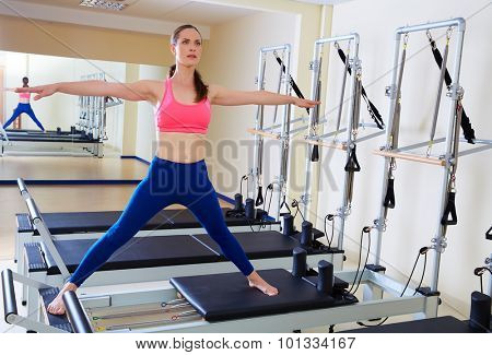 Pilates reformer woman side split exercise workout at gym indoor