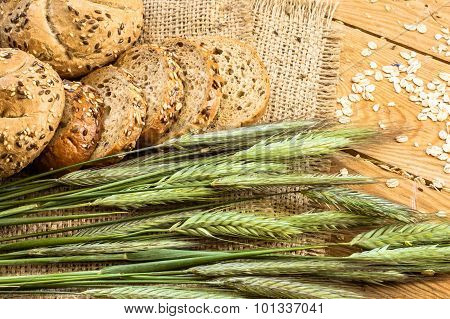 Whole Wheat Rye Bread Rolls With Ears Of Cereal Located On Wood Background. Rustic Arrangement.