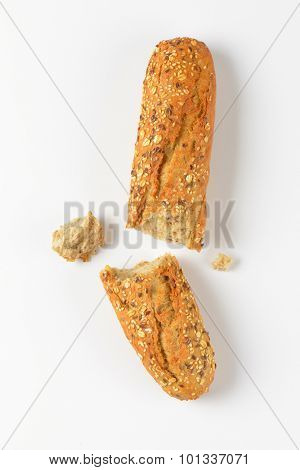 halved bread roll with seeds on white background