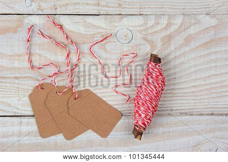 High angle view of blank Christmas Gift tags next to a spool of string on a whitewashed rustic wood table. The tags are blank and the string is wound around a twig.