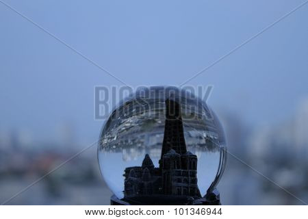 Toy tower in snow globe over real city buildings