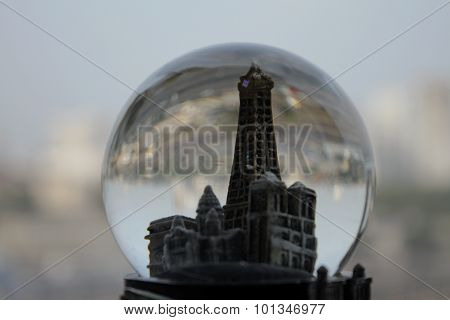 Toy tower in snow glass over real city buildings