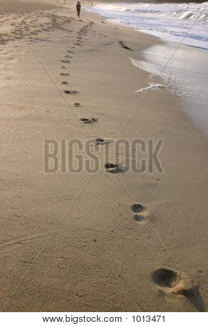 Footprints And A Woman In The Distance Jogging Along The Shore