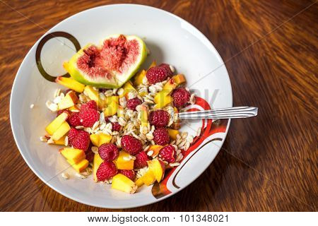 Granola With Red Rasberries With Fig As A Shape Of Heart In A White Bowl