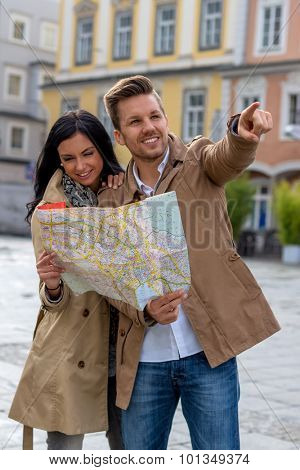 young couple with map and guide during a tour of town on vacation