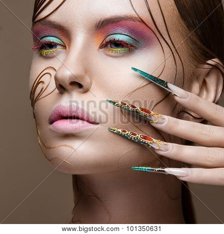 Beautiful girl with bright fashion make-up, creative hairstyle, long nails. Design manicure. Beauty