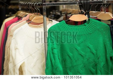 sweaters, sweatshirts on retail shop rack. Store interior.
