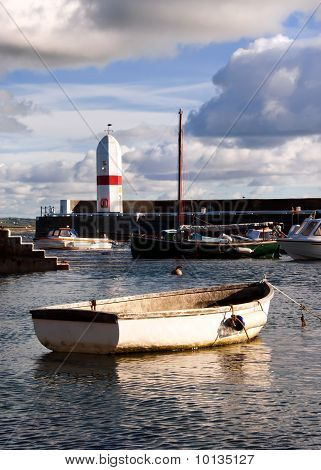 Small Boat Tied In A Harbour With Lighthouse