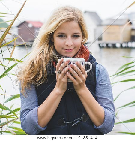 Happy free blonde woman enjoying hot beverages at lakeside. Autumn concept.