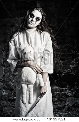 Horror Shot: Scary Monster Girl With Moppet Doll And Knife In Hands