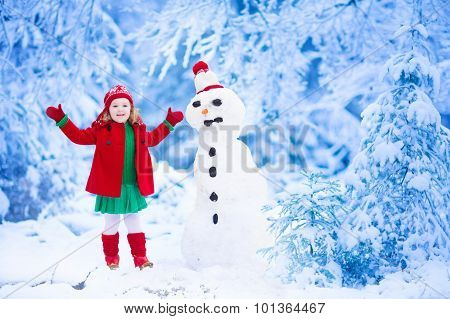 Little Girl Building A Snow Man In Winter