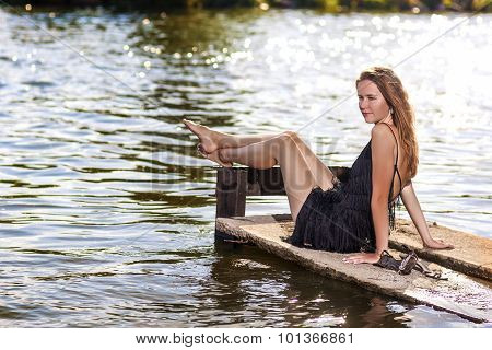 Sexy Sensual Caucasian Blond Woman Sitting On Pier Near Water. Relaxing Activity