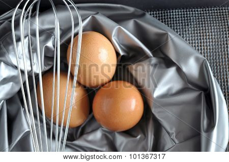 Close Up Whisk And Eggs On Silver Background