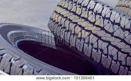 Closeup Of Stack Of Brand New Automobile Black Tyres With Numbers Placed Outdoors.