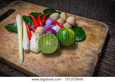 Kaffir Lime Leaf, Lemon, Lemongrass, Galangal, Chili, Onions And Straw Mushroom Over Chopping Block