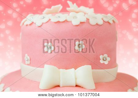 Pink Cake With Flower And Butterfly Decor Over Red Background With Heart Shaped Ornament