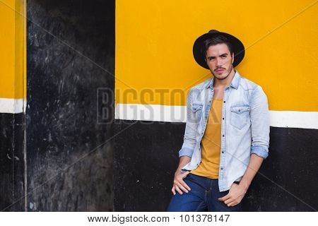 Young man posing in a urban background, with a cowboy style.