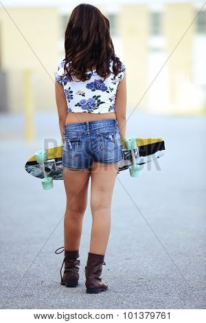 young girl carrying skate board