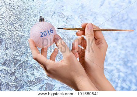 Women's Hands Drawing On Christmas Ball