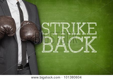 Strike back on blackboard with businessman on side