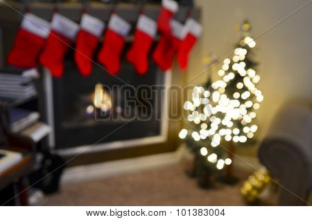 Detail of ront room decorated for christmas with christmas stockings and fireplace out of focus for background