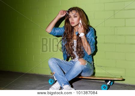 Beautiful Long-haired Lady With A Smatrphone Like Iphone Near A Green Brick Wall
