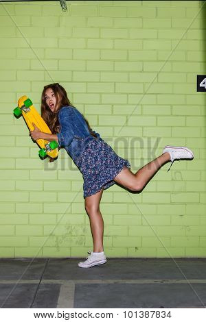 Beautiful Long-haired Woman With A Color Penny Shortboard Near A Green Brick Wall