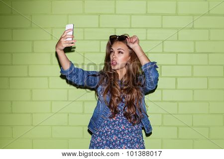 Beautiful Long-haired Lady With A Smartphone Near A Green Brick Wall