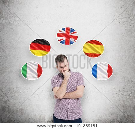 Young Man In Casual Shirt Holds His Chin And Thinks About Which Language To Study. Italian, German,