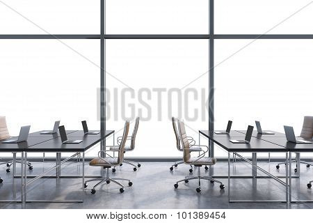 Workplaces In A Modern Panoramic Office, Copy Space In The Windows. Open Space. Black Tables And Bro