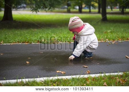 The Little Girl Looks In The Rain Puddle