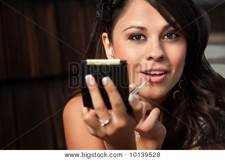 Beautiful Latina Woman With Compact Applying Lip Gloss