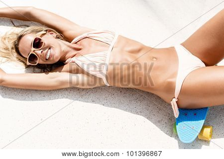Sexy Suntanned Lady Lying On The Blue Penny Board In The Park