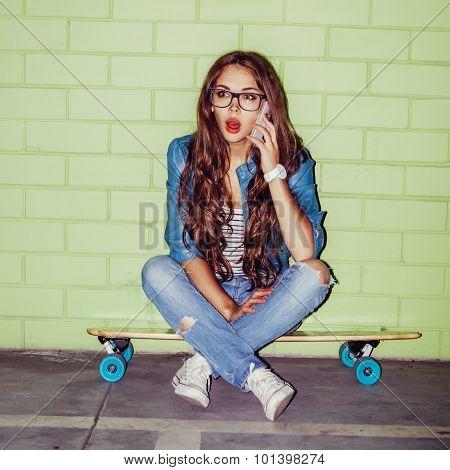 Beautiful Long-haired Girl With A Smatrphone Like Iphone Near A Green Brick Wall