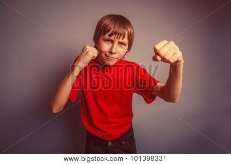 European-looking boy of ten years shows a fist, anger, threat on