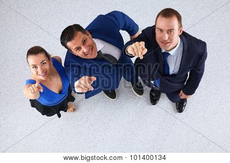 Business people standing together looking up and pointing at the camera- topview