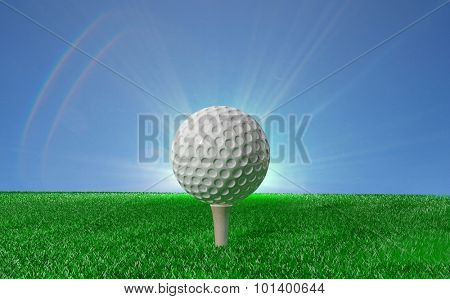 Golf ball on tee on green turf, with blue sky in background