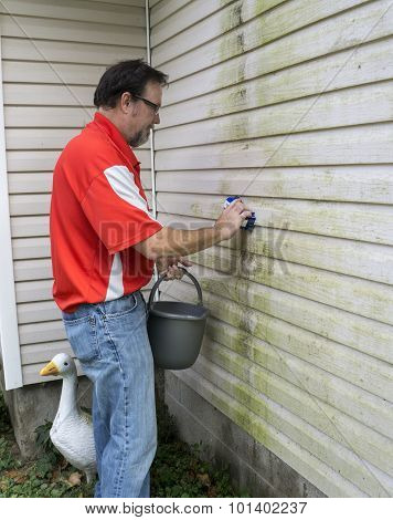 Contractor Cleaning Algae And Mold From Vinyl Siding