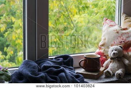 Coffee Mug, Book, Teddy Bear, Pillows And A Plaid On The Light Wooden Surface Against Window With Ra