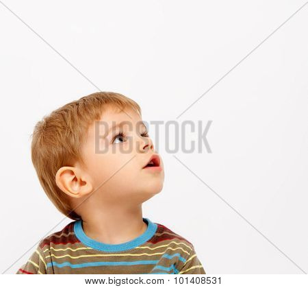 Boy in winter clothes looking up on white background