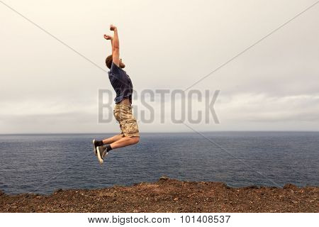 Success or win concept - joyful man jumping outdoor