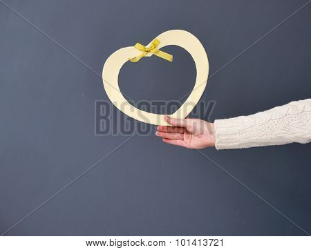 Closeup Portrait Of Young Female Holding Heart Shape Isolated On Gray Background