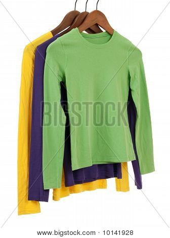 Three Long Sleeved Shirts On Wooden Hangers