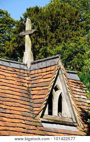 Dormer window in roof with stone cross.