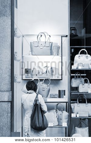 woman Considers Bags In A Show-window Of Boutique .