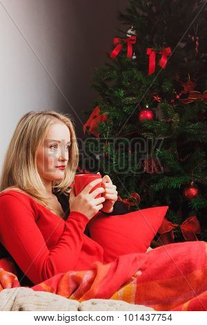 Nice woman sits in round chair with red mug