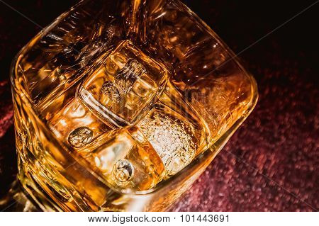 Top Of View Of Glass Of Whiskey On Wood Table With Focus On Ices, Warm Atmosphere