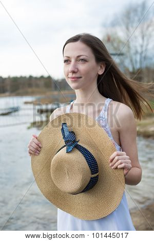 Freckled Happy Girl Holding Hat And Looking Away