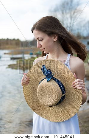 Freckled Happy Girl Holding Hat And Looking To The Side